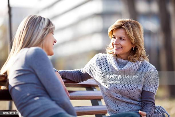 Two girlfriends sitting on park bench and talking