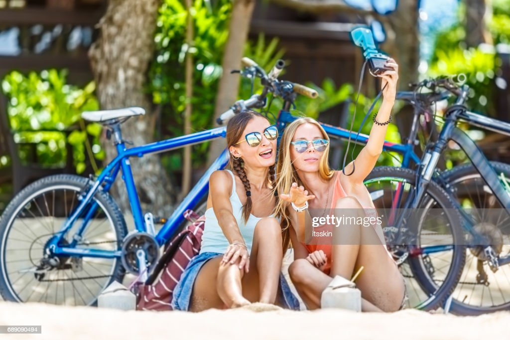 Two girlfriends sitting on sand, having rest in the shade of trees, taking selfies. Bicycles behind them : Stock Photo