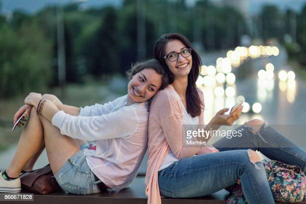 Two girlfriends sitting together with their phones in hands