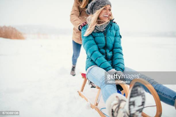 Two girlfriends sledding in a winter day