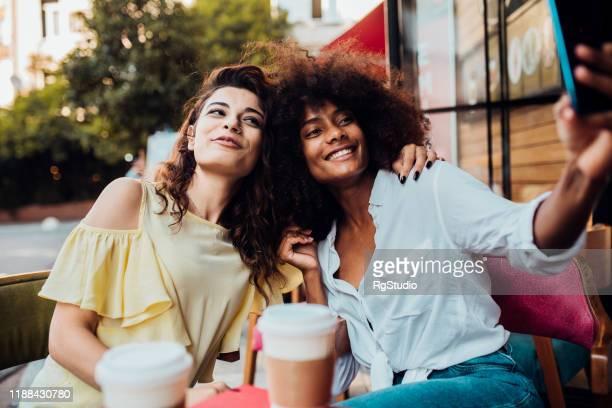 zwei freundinnen machen ein selfie im café - weibliche freundschaft stock-fotos und bilder