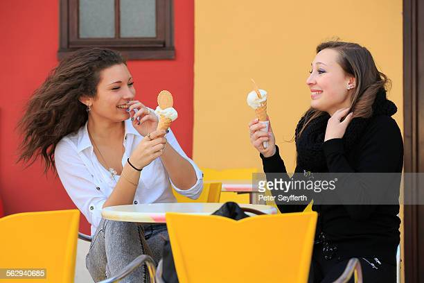 Two girlfriends, teenagers, eating ice cream from cone on the terrace an ice cream parlour, Menton, Alpes-Maritimes, Provence-Alpes-Cote dAzur, France