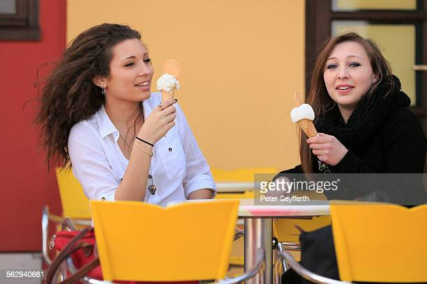 Two girlfriends, teenagers, eating ice cream from cones on the terrace an ice cream parlour, Menton, Alpes-Maritimes, Provence-Alpes-Cote dAzur, France