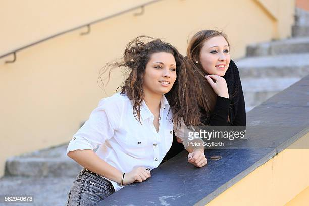 Two girlfriends, teenagers, leaning on the railing of a staircase, looking into the distance, Menton, Alpes-Maritimes, Provence-Alpes-Cote dAzur, France