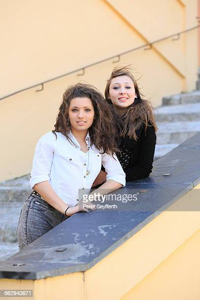 Two girlfriends, teenagers, posing on a staircase, Menton, Alpes-Maritimes, Provence-Alpes-Cote dAzur, France