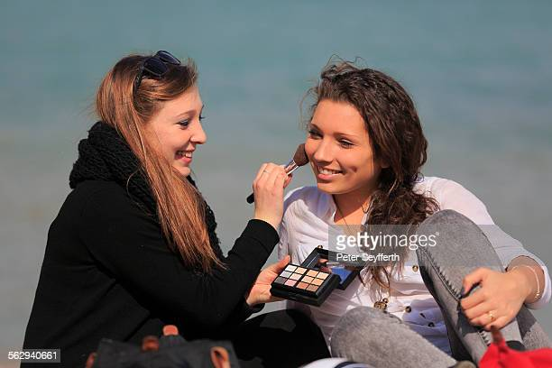 Two girlfriends, teenagers, sitting on the beach, applying makeup on each other, Menton, Alpes-Maritimes, Provence Alpes, France