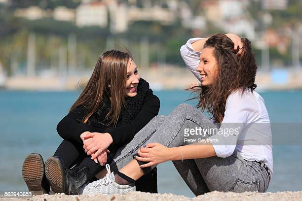 Two girlfriends, teenagers, sitting on the beach, Menton, Alpes-Maritimes, Provence Alpes, France