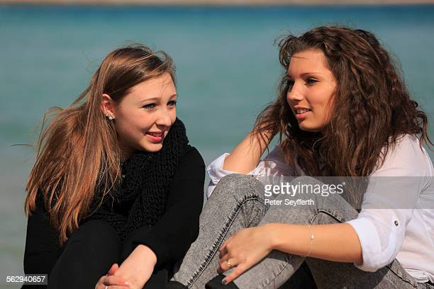 Two girlfriends, teenagers sitting on the beach, Menton, Alpes-Maritimes, Provence Alpes, France