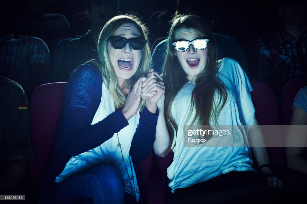 Two girlfriends wearing 3D glasses at the movies : Stock Photo