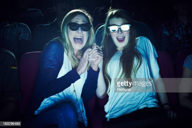 two girlfriends wearing 3d glasses at the movies - terrified stock pictures, royalty-free photos & images