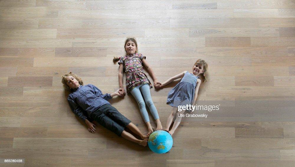Children standing on a globe : News Photo