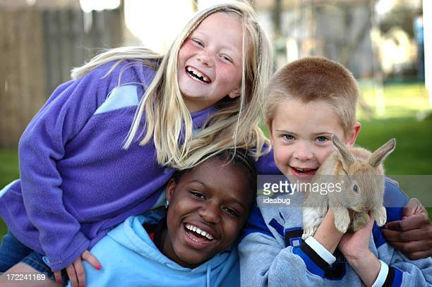 Two Girls and a Boy Laughing Together Outside with Bunny