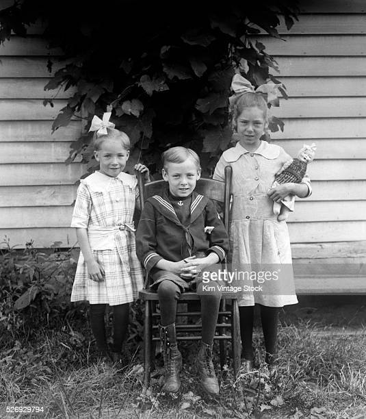 Two girls and a boy pose together outside the family home