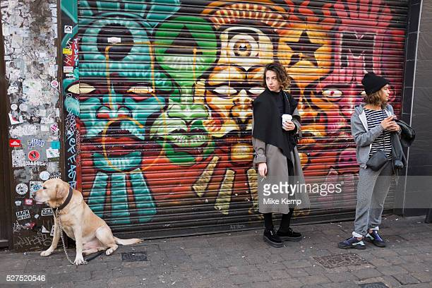 Two girls and a dog outside a painted shutters on Brick Lane in the East End of London UK Street art in the East End of London is an ever changing...