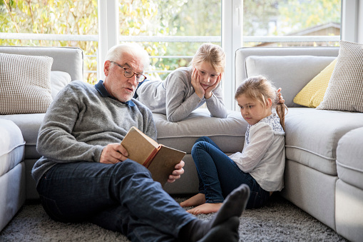 Two girls and grandfather reading book in living room - gettyimageskorea