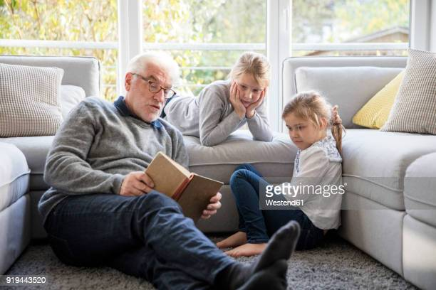 two girls and grandfather reading book in living room - grandfather stock pictures, royalty-free photos & images