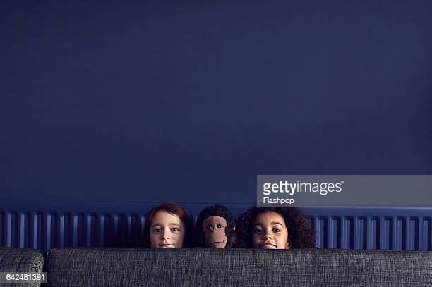two girls and toy monkey peering over sofa - donkerblauw stockfoto's en -beelden