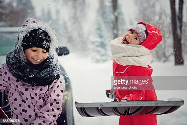 Two girls are cleaning the snow