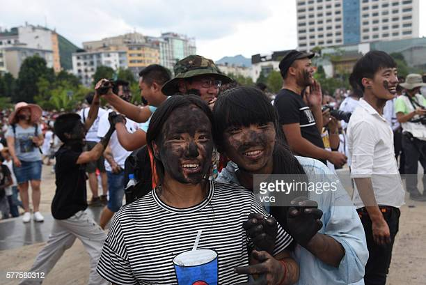 Two girls are daubed rice ash on faces during the Face Painting Festival in Puzhehei Resort of Qiubei County on July 18, 2016 in Wenshan Prefecture,...