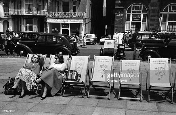 Two girls are pictured seating in deck chairs on the promenade at Brighton. Original Publication: Picture Post - 8568 - Girls In Summer Dresses -...