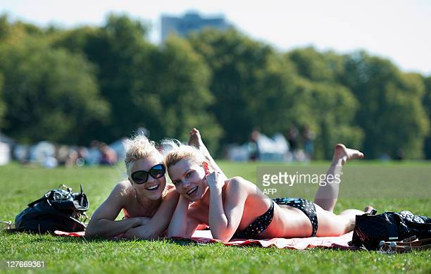 Two girls are pictured while sunbathing in Hyde Park central London on September 30 2011 Sunseekers today were continuing to enjoy the unusual...