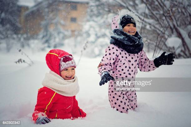 Two girls are playing in the snow
