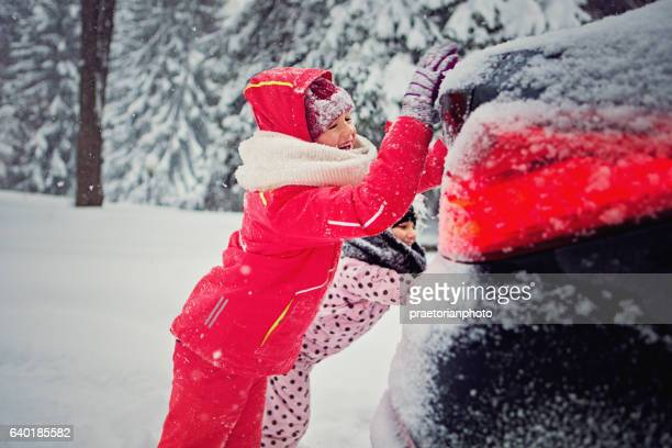 Two girls are pushing a car stuck in the snow