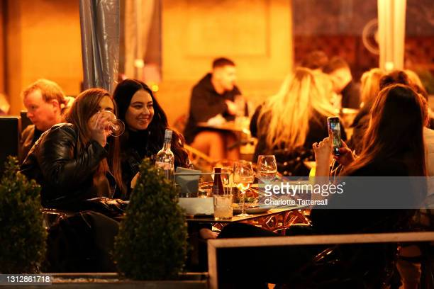Two girls are seen having their photograph taken while drinking in outdoor seating venues on April 16, 2021 in Manchester, England. Pubs and...