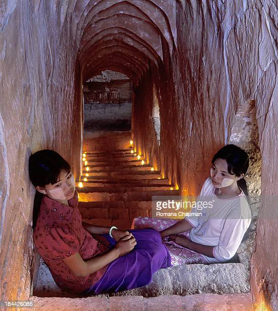 Two girls are sitting on stairs leading down to the groundfloor of a temple in bagan. On their cheeks they have thanaka paste, a paste made from a...