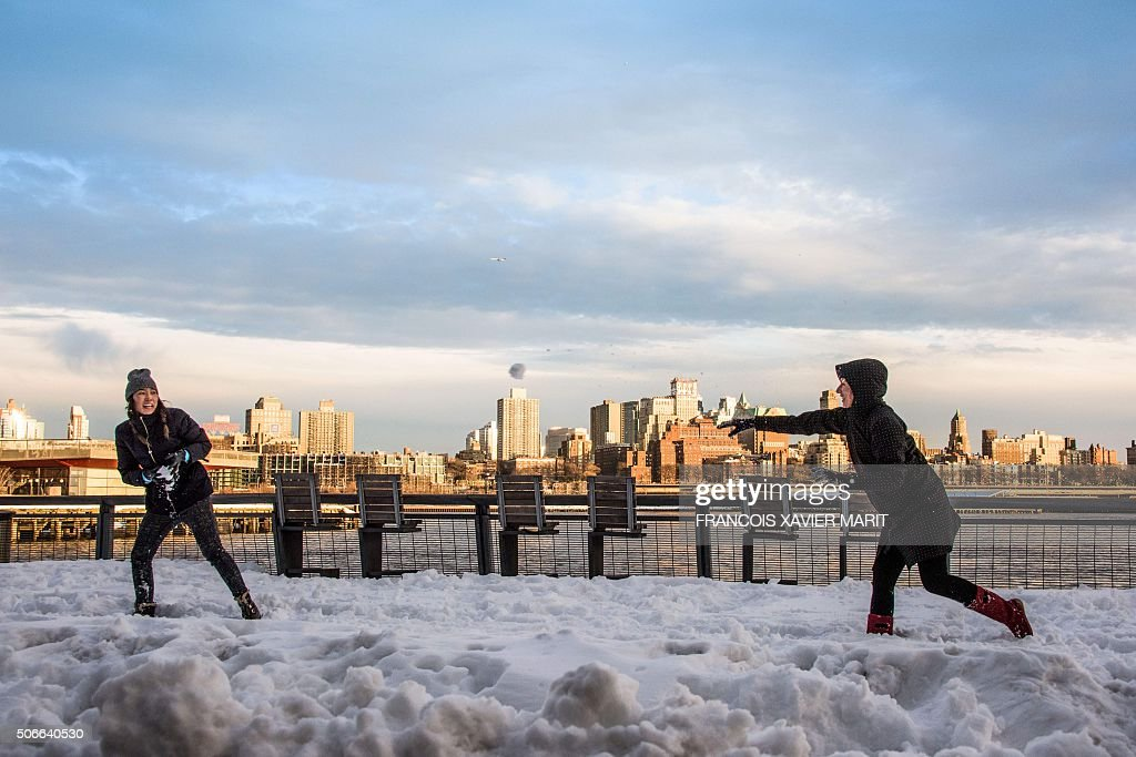 TOPSHOT - Two girls are throwing snow balls at each other on the banks of Financial District with Brooklyn in the background on January 24, 2016 in New York. A massive blizzard that claimed at least 16 lives in the eastern United States finally appeared to be winding down Sunday, giving snowbound residents the chance to begin digging out. / AFP / FRANCOIS