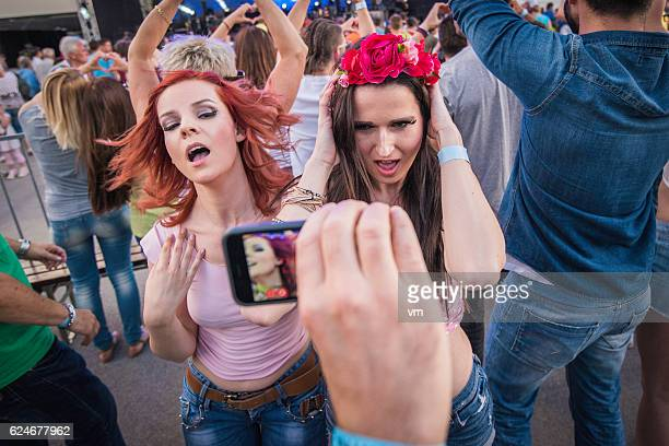 Two girls at a concert posing for a photo