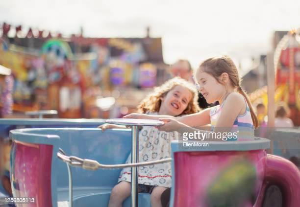 見本市会場で二人の女の子 - 遊園地の乗り物 ストックフォトと画像
