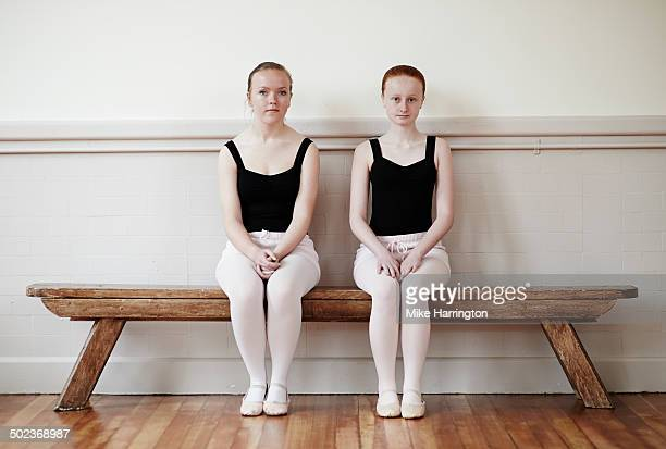 Two girls at ballet sitting on bench.