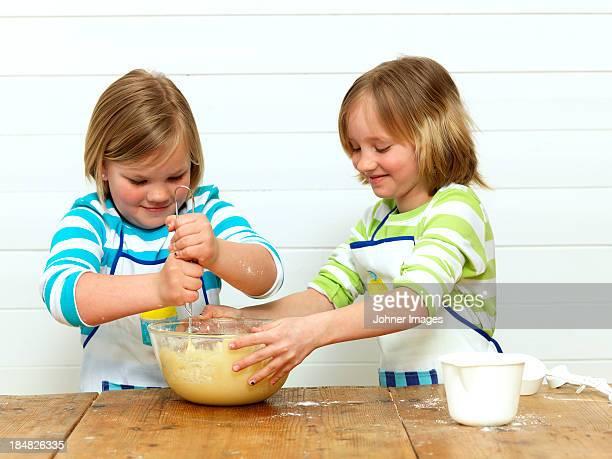 Two girls baking cake in kitchen