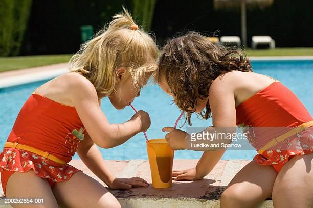 two girls (4-6) by poolside drinking from beaker through straws - alleen meisjes stockfoto's en -beelden