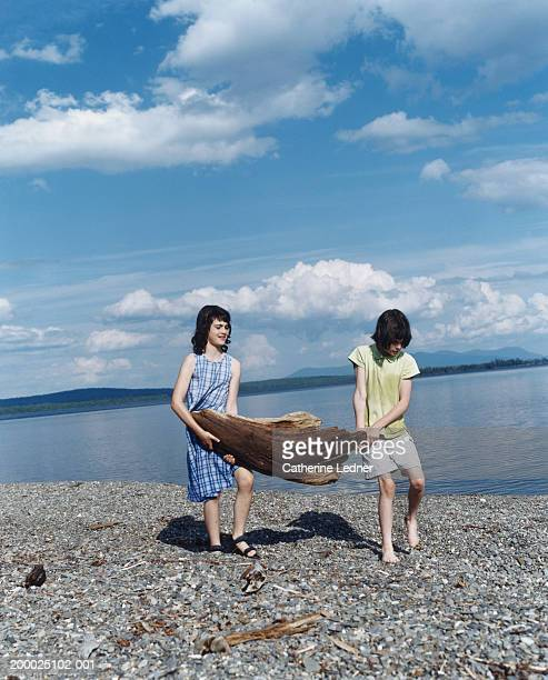 two girls (11-13) carrying log across beach - moosehead lake stock photos and pictures