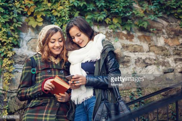Two girls, cell phone and a book