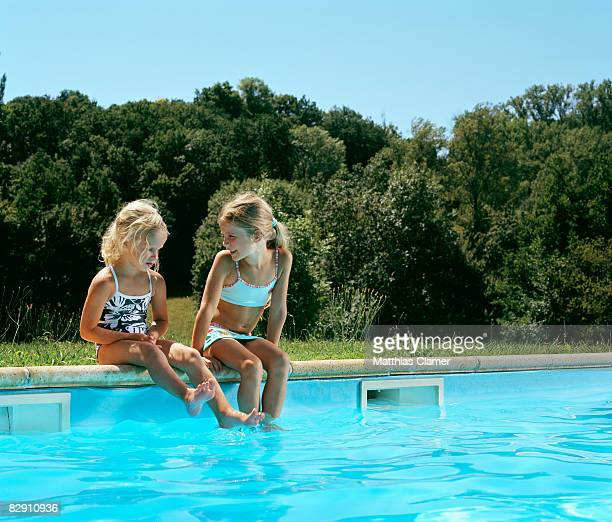 two girls chat by the pool side