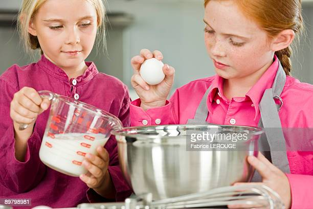 Two girls cooking food in the kitchen