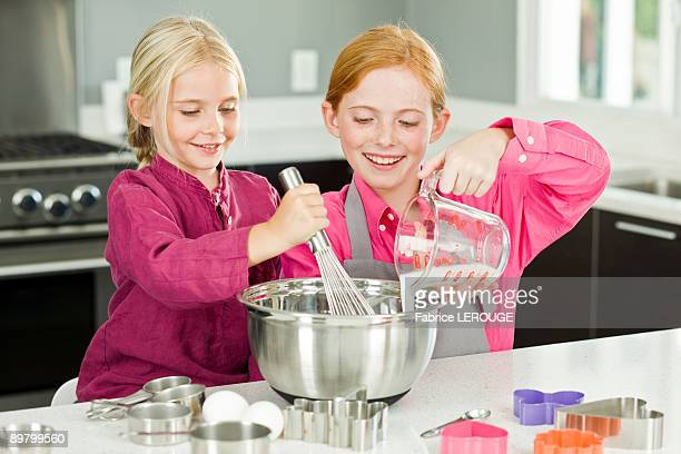 two girls cooking food in the kitchen - measuring cup stock pictures, royalty-free photos & images