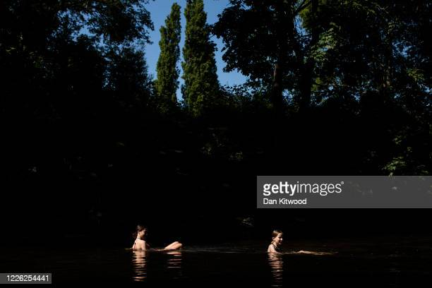 Two girls cool off in the River Lea on May 21 2020 in London United Kingdom This week temperatures reached 28 degrees celsius in the UK as many...