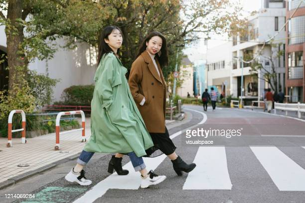 two girls cossing the street - khaki stock pictures, royalty-free photos & images