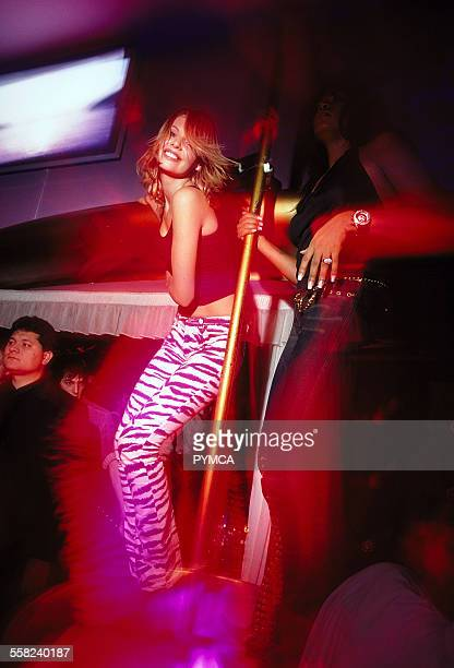 Two girls dancing around a pole at VIP club Paris October 2002