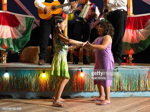 Zwei Mädchen (8-10), Tanz, band spielen auf der Bühne im Hintergrund