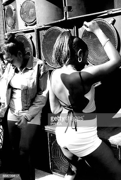 Two girls dancing by wall of speakers Notting Hill Carnival London UK 1999