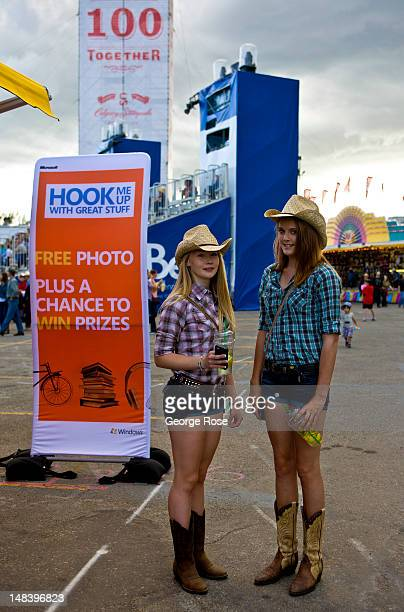 Two girls decked out in country western clothing pose for a photo on July 5 2012 in Calgary Canada Calgary Stampede is the world's largest outdoor...