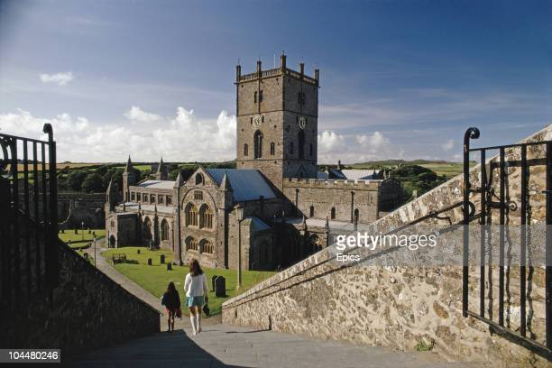 Two girls descend the steps leading down to St Davids Cathedral Pembrokeshire Wales August 1970