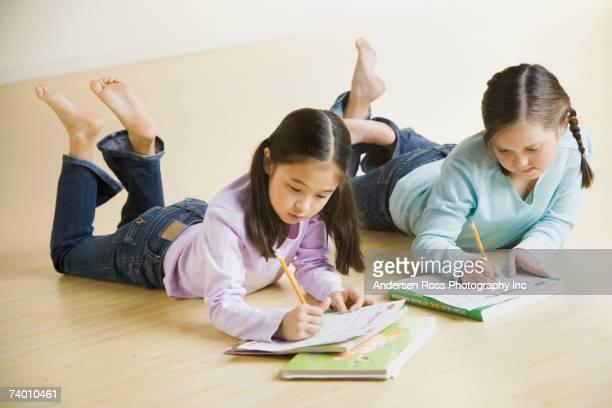 Two girls doing homework on floor