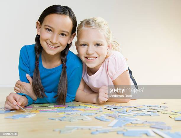 Two girls (8-10) doing jigsaw puzzle on wooden floor