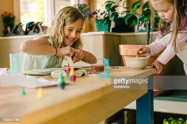 two girls doing science experiment at table - heshphoto stockfoto's en -beelden